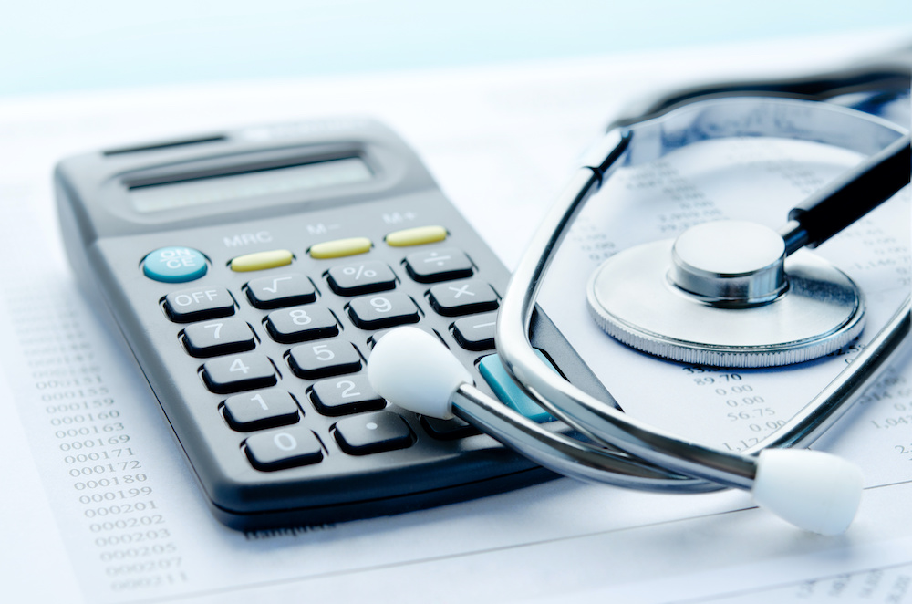 A stethoscope and calculator sit together to represent medical equipment planning.