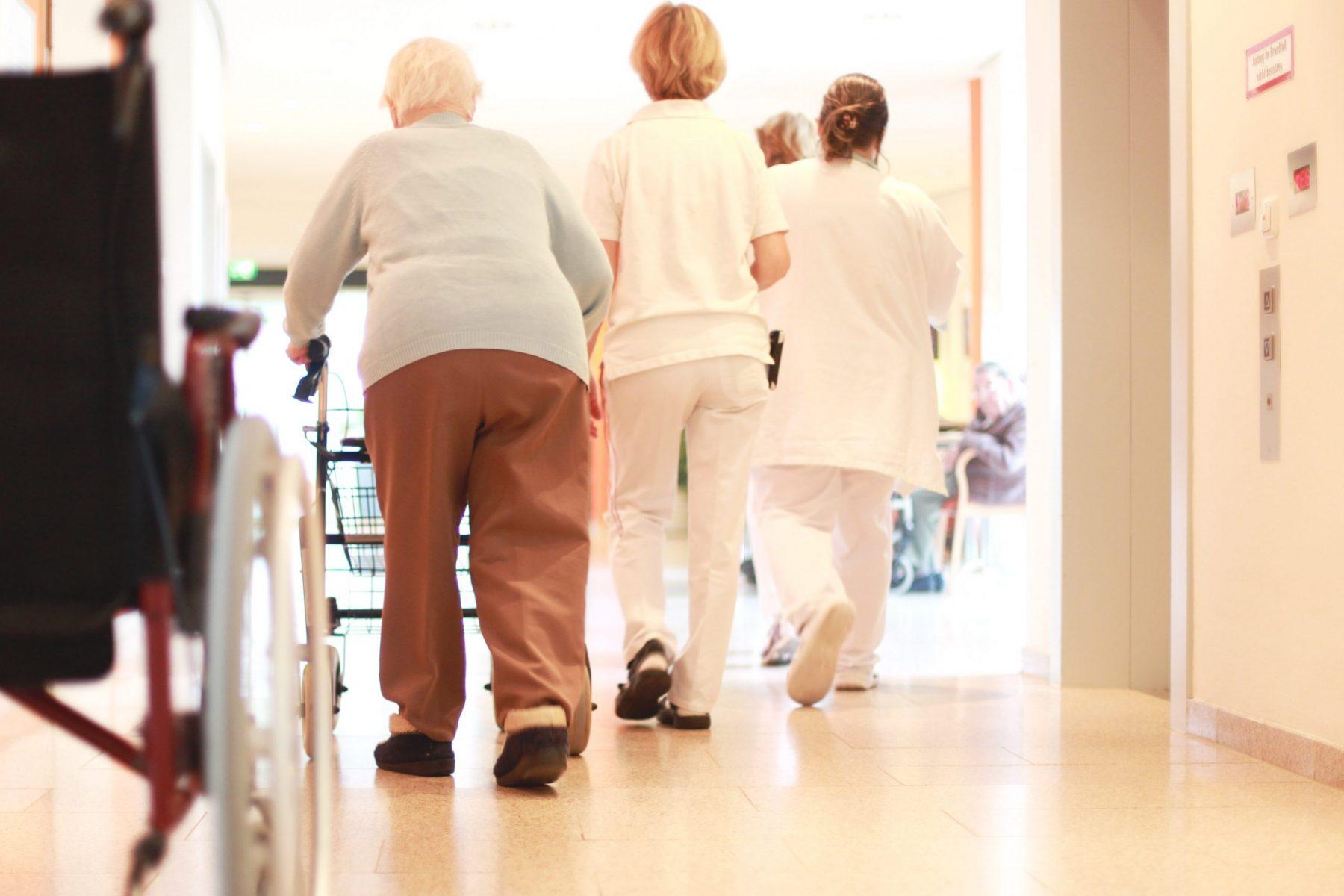 Elderly woman accompanied by nurses moves down a hallway