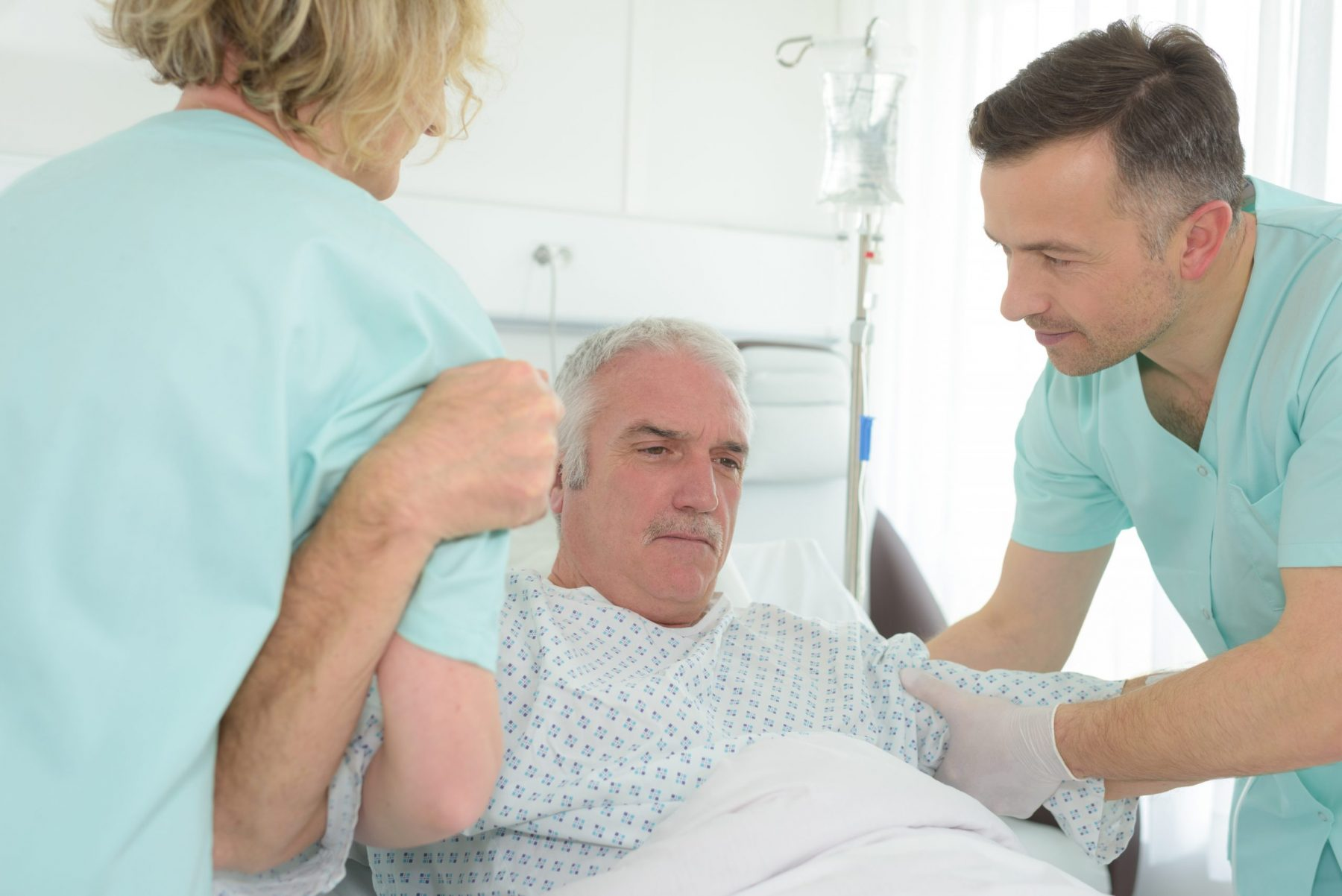 Medical workers helping patient rise from bed
