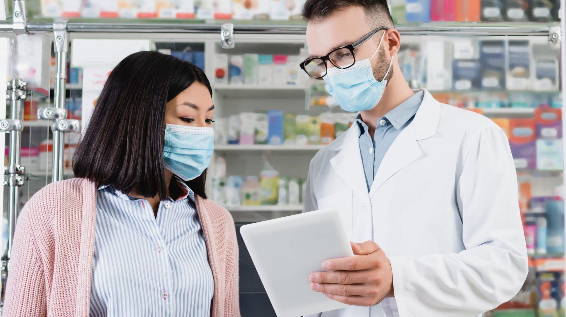 Pharmacist in eyeglasses and medical mask holding digital tablet near asian woman in drugstore, banner