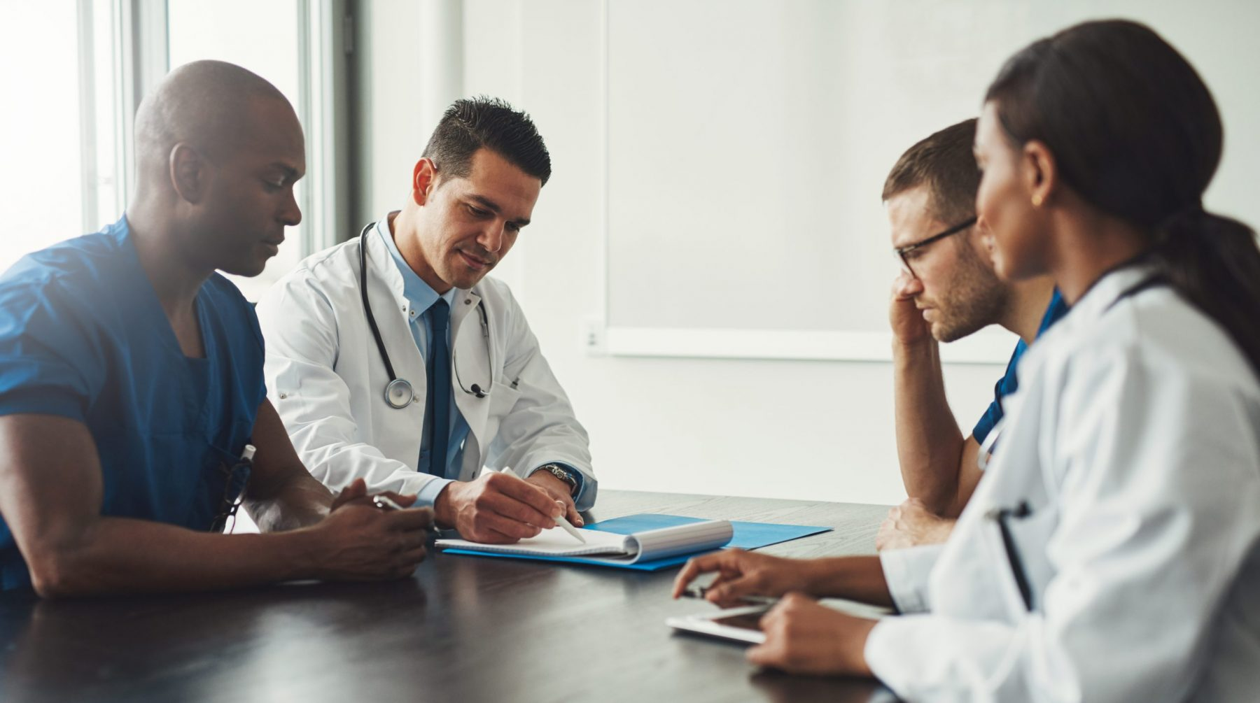 Young medical personal people on staff meeting sitting in front of each other at table in white coats and blue uniform shirts