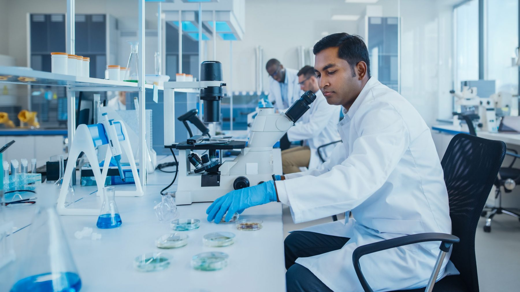 Man in lab coat in front of microscope with petri dishes on surface of the table